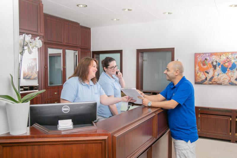 Zahnarzt Koblenz Karthause - Fernandez steht mit zwei Mitarbeiterinnen am Empfang der Praxis