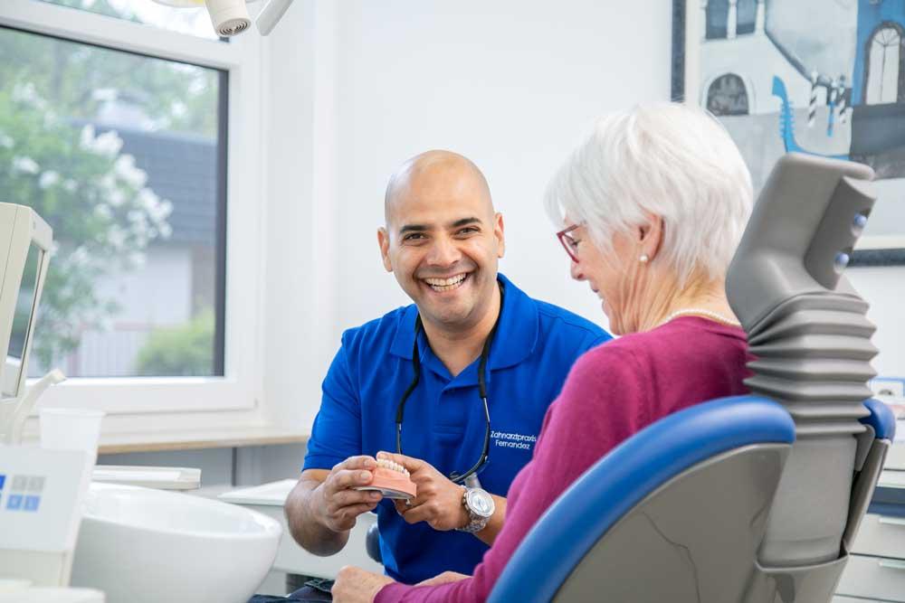 Zahnarzt Koblenz Karthause - Fernandez - Leistungen - Zahnarzt Fernandez berät ältere Dame auf dem Zahnarztstuhl zu hochwertiger Prothetik